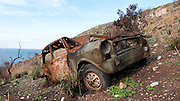 An abandoned car on the coast near Castellamare del Golfo, that has been burnt by brush fire. Northwest Sicily, Italy.