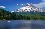 Trillium Lake south of Mount Hood with view of the mountain, two fishermen in a canoe on the lake.<br /> .....<br /> Trillium Lake is a lake situated 7.5 miles south-southwest of Mount Hood in the U.S. state of Oregon. It is formed by a dam at the headwaters of Mud Creek, tributary to the Salmon River. It was created by the state Department of Fish and Wildlife in 1960. The area which is now the lake was part of the Barlow Road, a component of the Oregon Trail. A log road across marshes allowed immigrants to pass to Summit Meadow, which was a toll station 1866—1870. Trillium is a genus of flowers particularly noticeable in the area. The lake is popular for fishing, camping and photography, often clearly reflecting Mount Hood. Adjacent Trillium Lake Campground is administered by the Zigzag Ranger District of the Mount Hood National Forest. The large campground features a seasonal boat ramp and wheelchair-accessible floating dock. The lake is a very popular Nordic skiing destination from a trailhead across U.S. Route 26 from Snow Bunny. Some resources note its popularity on afternoons and weekends.