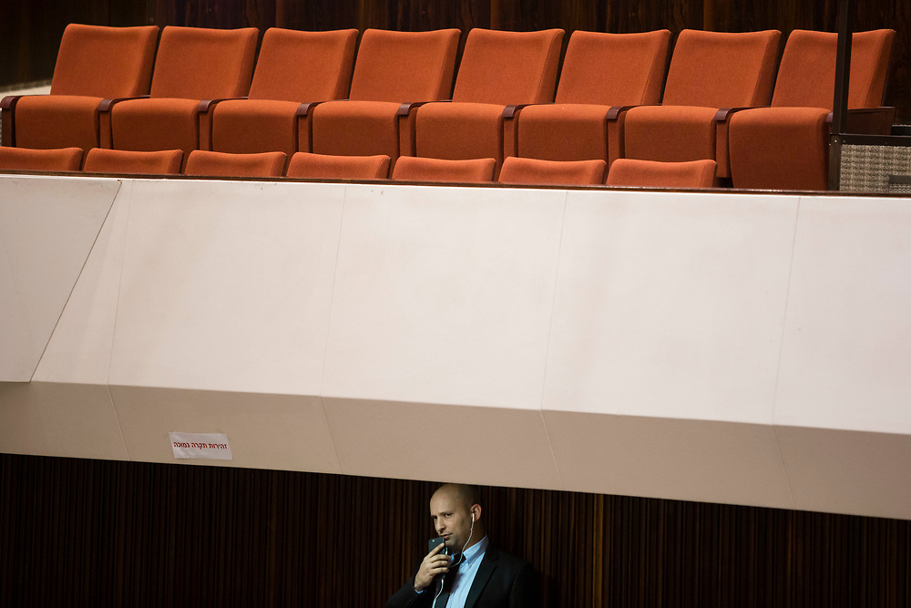 Israeli Minister of Economics and leader of the Jewish Home party Naftali Bennett is seen using his mobile phone during a session of the Knesset, Israel's parliament in Jerusalem, on January 21, 2015. The Knesset approved a bill to raise the minimum wage in Israel.