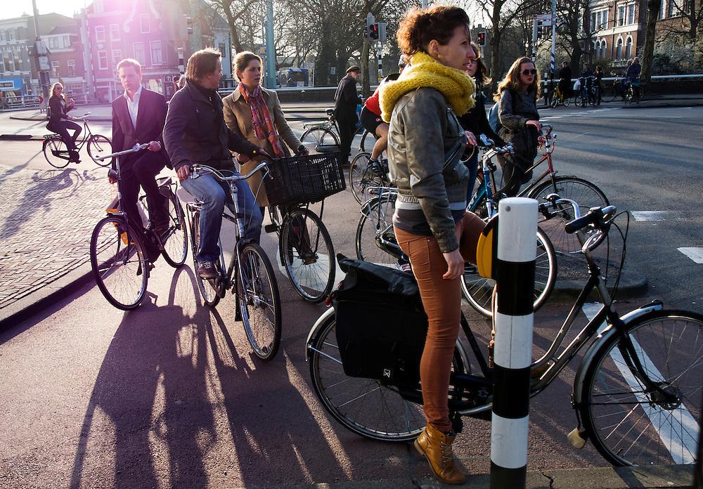 In Utrecht passeert een fietsende man in pak een rij fietsers die staan opgesteld bij het verkeerslicht aan het Ledig Erf. Er is nauwelijks ruimte om te passeren, het verkeerspunt is te krap aangelegd.<br /> <br /> In Utrecht a cycling man in a suit is passing a cue cyclists waiting for the traffic light. There is hardly room to pass, the crossing is too small.