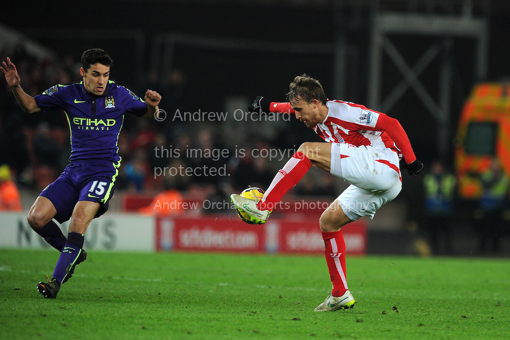 Marc Muniesa of Stoke city is challenged by Jesus Navas of Man city (l).  Barclays Premier League match, Stoke city v Manchester city at the Britannia Stadium in Stoke on Trent , Staffs on Wed 11th Feb 2015.<br /> pic by Andrew Orchard, Andrew Orchard sports photography.