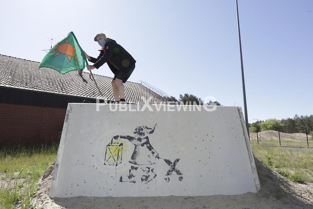 BI-Pressesprecher Wolfgang Ehmke hisst die Fahne über dem als Mahnmal aufgestellten Reststück der Mauer, die bis 2019 das Erkundungsbergwerk in Gorleben hermetische angeriegelt hat.<br /> <br /> Ort: Gorleben<br /> Copyright: Andreas Conradt<br /> Quelle: PubliXviewinG