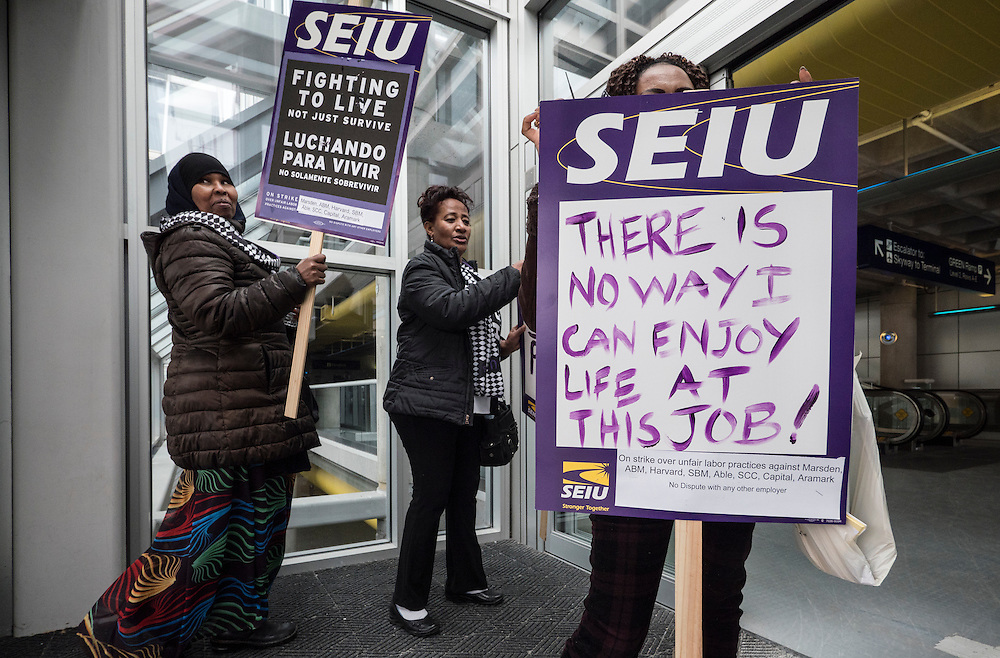 Shewanesh Wedajo, right, displays her sign as Twin Cities janitors represented by Service Employees International Union, as well as some supporters, picket for a wage increase at Minneapolis-St. Paul International Airport's Terminal 1 February 17, 2016.  The union is asking for $15 for both full and part-time workers.