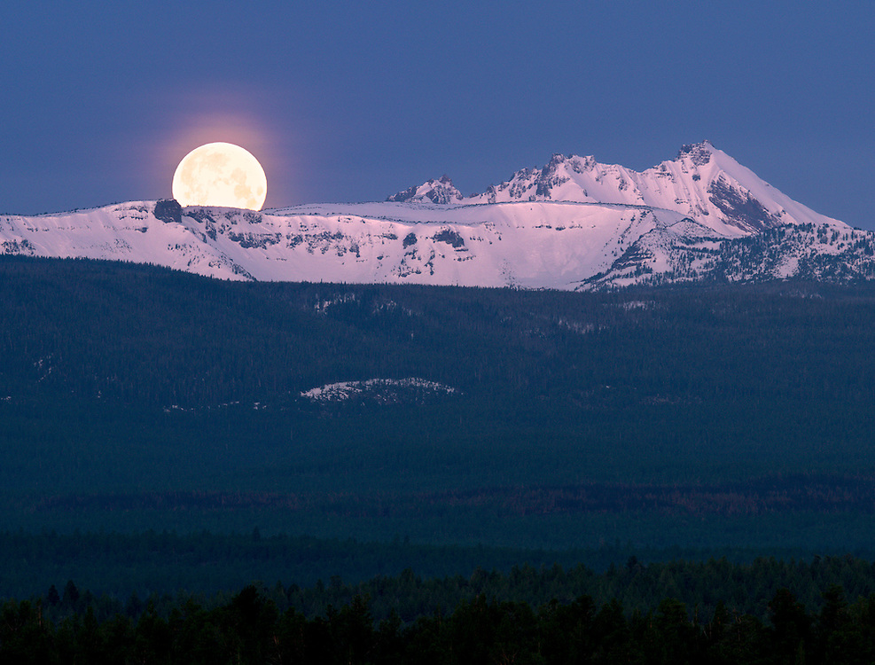 """A setting """"super-moon"""" sinks below the snow-capped summit of Broken Top peak, in the Cascade Range of Central Oregon."""