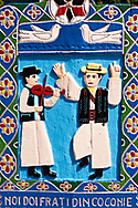 Tombstone showing a fiddler and a man dancing in traditional clothes,  The  Merry Cemetery ( Cimitirul Vesel ),  Săpânţa, Maramares, Northern Transylvania, Romania.  The naive folk art style of the tombstones created by woodcarver  Stan Ioan Pătraş (1909 - 1977) who created in his lifetime over 700 colourfully painted wooden tombstones with small relief portrait carvings of the deceased or with scenes depicting them at work or play or surprisingly showing the violent accident that killed them. Each tombstone has an inscription about the person, sometimes a light hearted  limerick in Romanian. .<br /> <br /> Visit our ROMANIA HISTORIC PLACXES PHOTO COLLECTIONS for more photos to download or buy as wall art prints https://funkystock.photoshelter.com/gallery-collection/Pictures-Images-of-Romania-Photos-of-Romanian-Historic-Landmark-Sites/C00001TITiQwAdS8