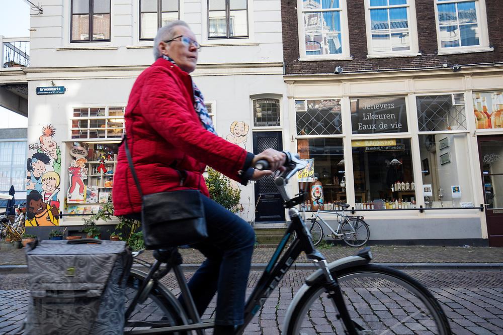 In Dordrecht rijdt een oudere vrouw op de fiets door de historische binnenstad langs een stripwinkel<br /> <br /> In Dordrecht a cyclist rides at the historical city center.