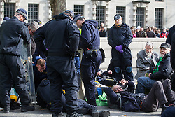 London, UK. 9 October, 2019. John Lynes, aged 91, and David, a great grandfather, both climate activists from Extinction Rebellion, wait to be arrested by police officers using Section 14 of the Public Order Act 1986 after blocking Whitehall on the third day of International Rebellion protests to demand a government declaration of a climate and ecological emergency, a commitment to halting biodiversity loss and net zero carbon emissions by 2025 and for the government to create and be led by the decisions of a Citizens' Assembly on climate and ecological justice.
