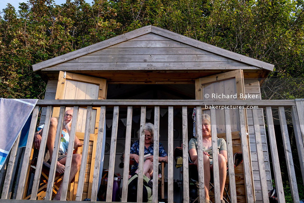Friends sit on the front porch of their beach hut, a relaxed afternoon spent swimming and resting, on 26th July 2021, in Whitstable, Kent, England.