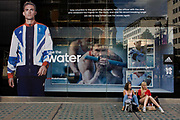 Two young women sit and rest from shopping beneath the inspiring image of Team GB gold medallist Ben Ainsley who adorns the exterior of the Adidas store in central London's Oxford Street, during the London 2012 Olympic Games. The ad is for sports footwear brand Adidas and their 'Take The Stage/Water' campaign which is viewable across Britain and to Britons who have been cheering these athletes who have been winning medals in numbers not seen for 100 years. Their heroic performances have surprised a host nation who until the victories, were largely anti-Olympics.