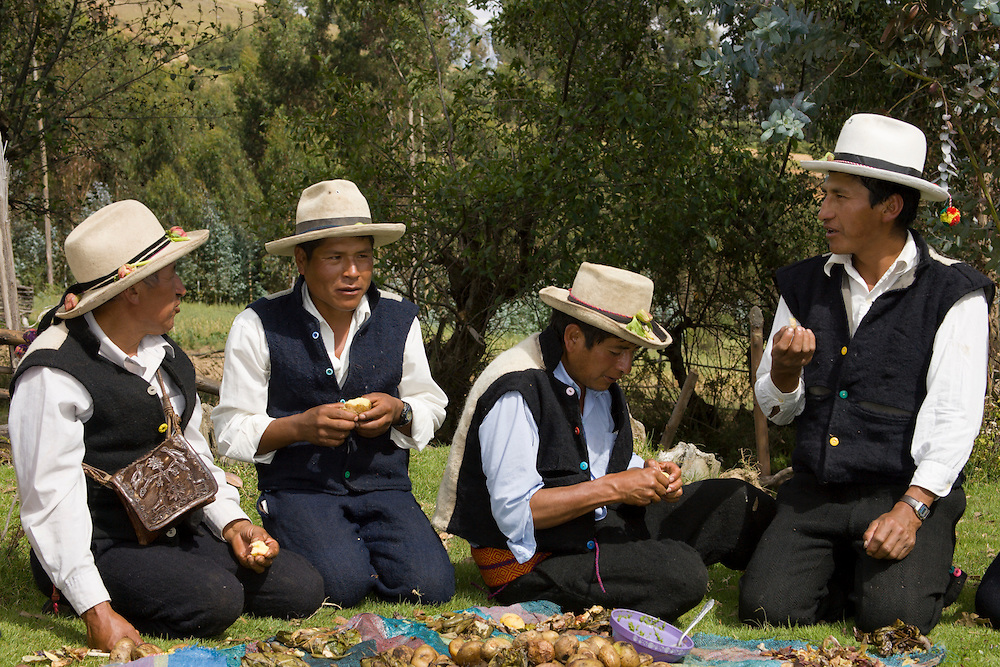 """Villagers in traditional clothing eat at """"pachamanca"""" feast, Vicos, Peru, South America  MR"""