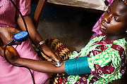 MCH nurse Helen Kumbasaquee measures the blood pressure of Yei Komeh, 19 years old, who is 32 weeks pregnant, at the Tombodu PHU in Tombodu, Sierra Leone on Wednesday March 17, 2010.