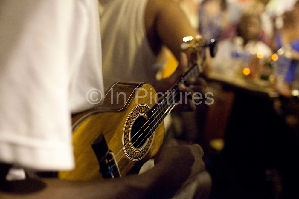 Man playing a ukelaly. Samba musicians playing with crowd around them, Pedra do Sal, the birthplace of Samba, in Gamboa district which was the neighbourhood where the ex slaves lived after abolition, sometimes referred to as the first favela. Rio de Janeiro, Brazil