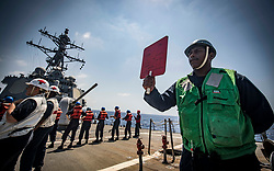 MEDITERRANEAN SEA (Aug. 10, 2018) Culinary Specialist 3rd Class Trevaughnn Mitchell signals to the fleet replenishment oiler USNS Leroy Grumman (T-AOE 195) from aboard the Arleigh Burke-class guided-missile destroyer USS Carney (DDG 64) during a replenishment-at-sea. Carney, forward-deployed to Rota, Spain, is on its fifth patrol in the U.S. 6th Fleet area of operations in support of regional allies and partners as well as U.S. national security interests in Europe and Africa. (U.S. Navy photo by Mass Communication Specialist 1st Class Ryan U. Kledzik/Released)180810-N-UY653-137