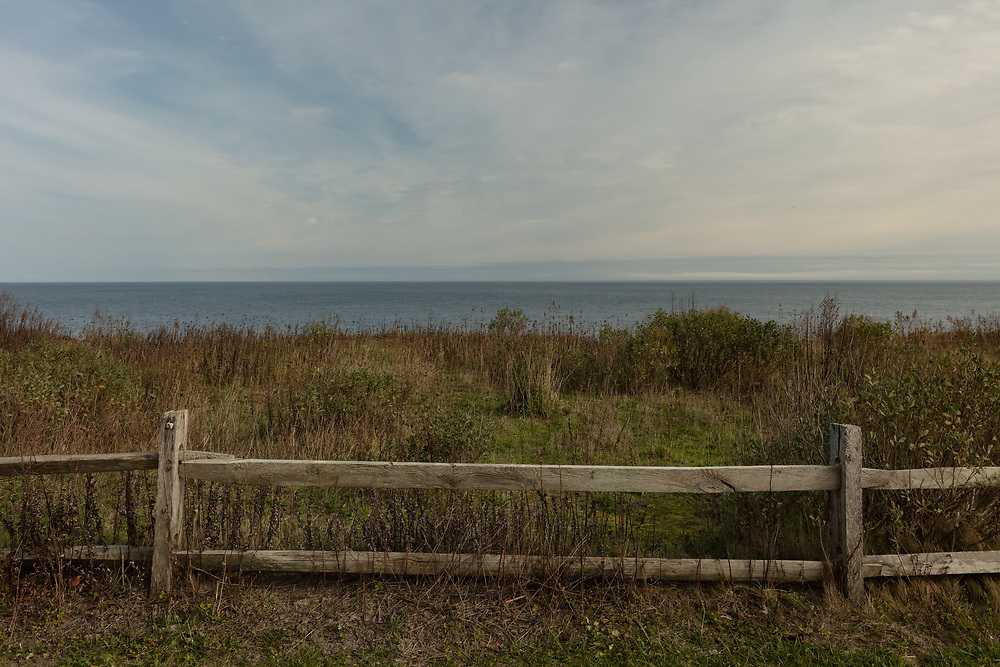 A wooden fence along the western Edge of Siasconset and. the vast expanse of the Atlantic Ocean.