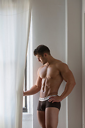 bodybuilder standing by a window in his underwear