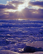 Winter sunrise over stacked ice plates along the shore of Lake Huron at Sturgeon Point, Sturgeon Point State Park, Michigan.