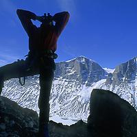 BAFFIN ISLAND, Nunavut, Canada. Alex Lowe (MR) peers thru binoculars at rock climbing route up huge Great Sail Peak, above Stewart Valley.