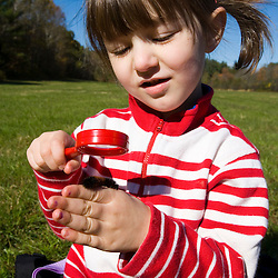 A young girl (age 4) studies a caterpillar on the Common Pasture in Newburyport, MA.