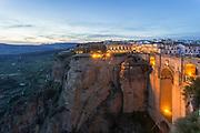 Puente Nuevo bridge and illuminated town at dusk, Ronda, Andalusia, Spain