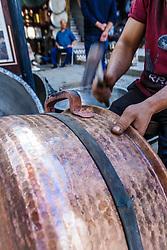 Craftsman working on copper cauldron, Fes al Bali medina, Fes, Morocco