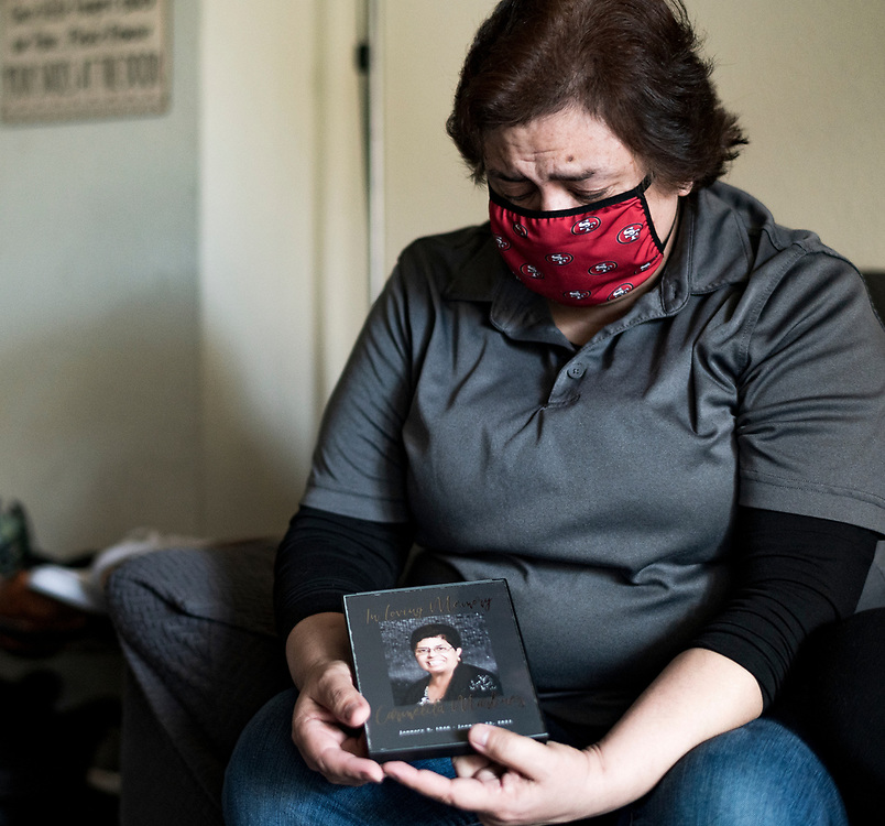 Stephanie Ybarra becomes emotional as she looks at a photo of her late-mother Carmelita Martinez in San Jose, Calif. on Feb. 19, 2021. Martinez died of COVID-19 in Salinas, Calif. on Jan. 23, 2021.