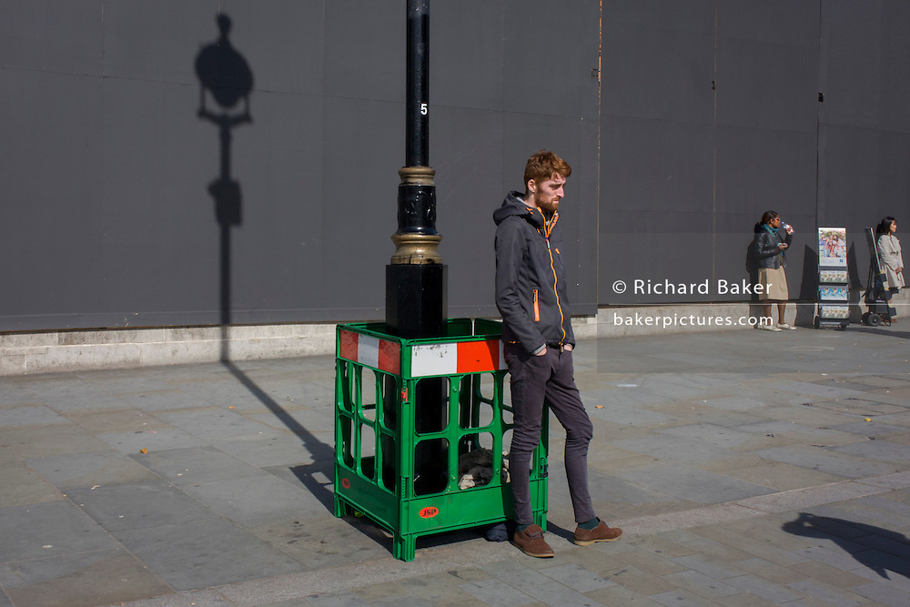 Lone man stands with a lamp post shadow against a grey construction hoarding in central London's Trafalgar Square.