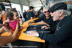 Willie G. and Nancy Davidson pause their autograph session during Wednesday's Ride-In Bike Show at the Harley-Davidson display to engage a little girl that came up with a fan at Daytona Bike Week. FL, USA. March 12, 2014.  Photography ©2014 Michael Lichter.