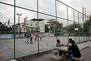 Young men / teenagers sit and chat beside a sports court. Cidade de Deus / City of God favela in Rio de Janeiro, made infamous by the film of the same name, is a bustling community of close to 100,000 inhabitants, with numerous cultural and social projects.