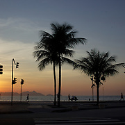 Praia de Copacabana at sunrise. Copacabana beach, as people exercise on one of the world's most famous urban beaches. The beach and hotel strip stretches for 1.5 miles (4km) from the Morro do Leme at the Northern end, to Arpoador at the South. Copacabana beach, Rio de Janeiro,  Brazil. 13th August 2010. Photo Tim Clayton.
