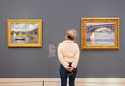 Visitor looking at paintings by Renoir and Gustave Caillebote  at new Museum Barberini in Potsdam Germany