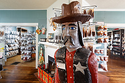 Wooden cowboy at Pendery's World of Chiles & Spices retail store, Fort Worth, Texas USA.