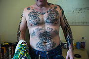 A prisoner showing off his tatoo's inside is cell at HMP/YOI Portland, Dorset, United Kingdom.