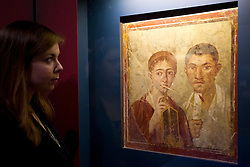 © Licensed to London News Pictures. 26/03/2013. London, UK. A British Museum employee views a wall painting of the baker Terentius Neo and his wife at the press view for a new exhibition at the museum, the picture was found in the remains of the baker's house destroyed in the Pompeii disaster. The exhibition, entitled 'Life and Death: Pompeii and Herculaneum', runs from the 28th of March to the 29th of September 2013 and looks at life in the Bay of Naples before and a the time of the catastrophic eruption of Mount Vesuvius; which buried the Roman towns of Pompeii and Herculaneum over 1600 years ago. Photo credit: Matt Cetti-Roberts/LNP