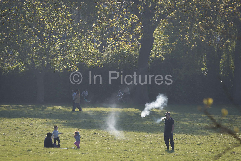 In the third week of the UK governments lockdown during the Coronavirus pandemic, when the daily UK death rate rose by another 761 to 12,868 and with nearly 100,000 reported cases from this respiratory desease, a man exhales vape smoke while taking daily exercise in Ruskin Park, a public green space in the south London borough of Lambeth, on 15th April 2020, in London, England.