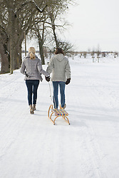 Couple pulling sledge in snow, Bavaria, Germany