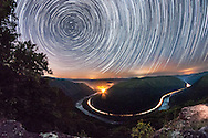 Time lapse of the stars as seen from the main overlook of the New River Gorge in Grandview, West Virginia at night.  A train passing through highlights the bend of the river as it curves through the mountains.