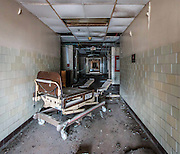 """Abandoned Charity Hospital<br /><br />Charity Hospital was founded in 1736, a public hospital built to care for the poor residents in the area.<br />By the 20th century, the city of New Orleans was rapidly expanding, and the demand for indigent medical services again exceeded Charity Hospital capacity. The current hospital building was completed and opened in 1939, and was the second largest hospital in the United States at the time. Serving one of the largest populations of uninsured citizens, Charity Hospital boasted the #2 Level I Trauma Center in the nation, with the #1 rank belonging to Cook County Hospital in Chicago, Illinois.<br />In 2005, Hurricane Katrina made landfall in Louisiana and initially, didn't cause much damage to the city of New Orleans. On August 29, flood walls and levees catastrophically failed, many were broken well below their thresholds. Mayor Nagin described the loss of life as """"significant"""" with reports of bodies floating on the water throughout the city, though primarily in the eastern portions.<br />Charity Hospital suffered severe flood damage during the storm. Bodies from the basement morgue floated down the halls, and doctors ordered to have them stacked in the stairwells. <br />The flood water trapped everyone inside, including patients and staff, for days without power and limited food, water, and medical supplies. Some patients were left to have to hand pump oxygen themselves. At one point, the most critical patients were paddled across the flood streets to a nearby parking deck where they were then carried up 7 flights of stairs to the top, where rescue helicopters were waiting. Many patients died there on the parking deck awaiting rescue. It wasn't until nearly a week later that the last person was rescued from Charity Hospital.<br />After the storm, there was a large push to reopen the hospital. The National Guard and US Army Corps of Engineers decontaminated and cleaned the bottom floors of the hospital, pumping out the water"""