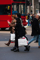 "London, December 23rd 2014. Dubbed by retailers as the ""Golden Hour"" thousands of shoppers use their lunch hour to do some last minute Christmas shopping in London's West End. PICTURED: Shoppers with their fistfuls of bags at Oxford Circus."
