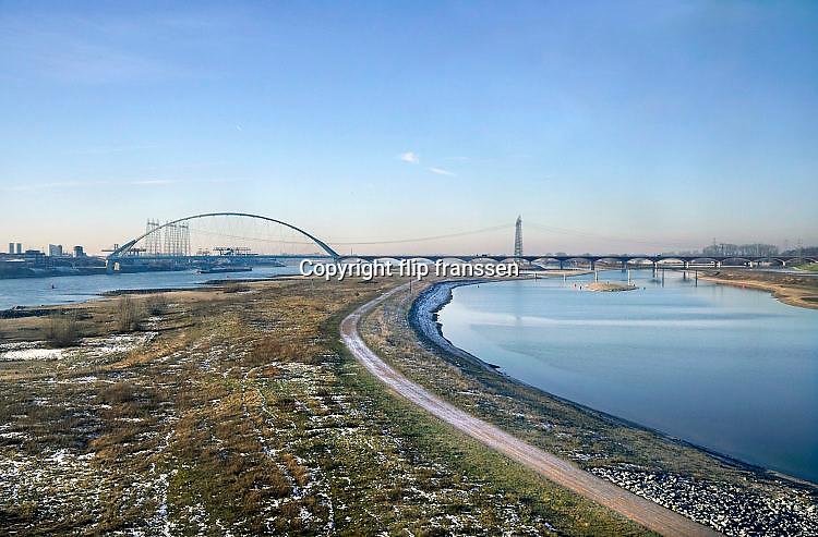 Nederland, Nijmegen, 19-1-2017De bijna 4 km. lange nevengeul van de Waal bij Lent. Op de achtergrond de waalbrug De Oversteek. Grootste onderdeel van de vele werken van Rijkswaterstaat om bij hoogwater een betere waterafvoer in de rivier te hebben. Het dorp veurlent komt op een kunstmatig eiland te liggen met twee kleinere bruggen als ontsluiting. Een voetgangersbrug, de steltlopersbrug voor wandelaars naar het recreatiegebied. Ruimte voor de rivier, water, waal. In de nieuwe dijk wordt een drempel gebouwd die stapsgewijs water doorlaat en bij hoogwater overloopt. The Netherlands, Nijmegen Measures taken by Nijmegen to give the river Waal, Rhine, more space to flow during highwater and to prevent the risk of flooding. Room for the river. Reducing the level, waterlevel. Large project to create a new paralel gully, an extra flow of water, so the river can drain more water during highwater. Due to climate change and expected rise, increase of the sealevel, the Dutch continue to protect their land from the water. Foto: Flip Franssen