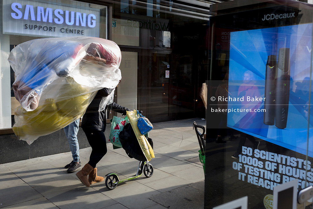 A lady pushes a scooter while carrying inflated party balloons past advertising at a bus stop in Kingston town centre, on 13th November 2019, in London, England.