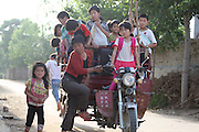 ZHONGMU, CHINA - (CHINA OUT) <br /> <br /> Overloaded 'School Bus' In Henan<br /> A woman drives a motor tricycle loaded with 31 pupils on a country road in Zhongmu County, Henan Province of China. The driver was a middle-aged woman, who had to tilted her head to see the road ahead as her daughter was standing on the tank right in front of her. All the kids on her tricycle, who attend the same school nearby, are children of the local residents, she told the journalist. When asked if she was aware of the safety hazard, the woman said she has to use the pedicab as the school doesn't have any real school buses. <br /> ©Exclusivepix