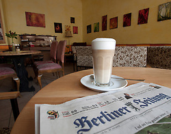 Detail of coffee and local newspaper in bohemian cafe Tasso on Karl Marx Allee in former East Berlin Germany