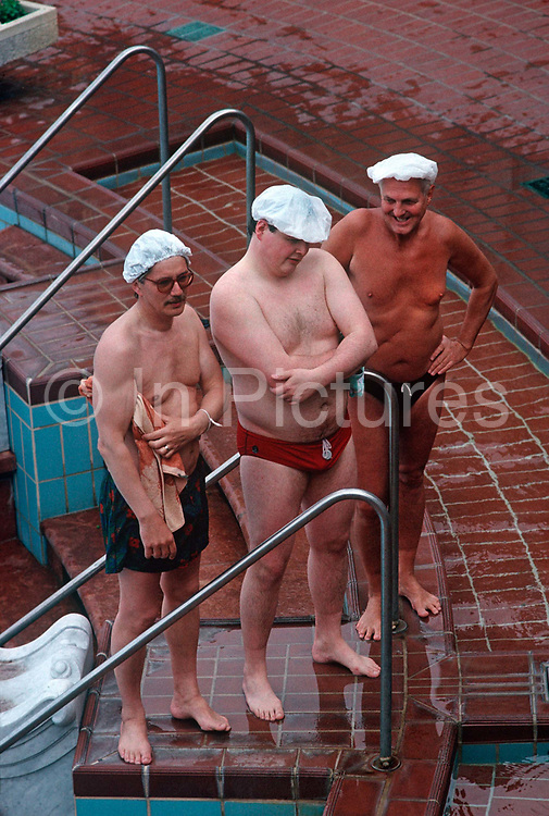 Three Hungarian men stand at the thermal poolside wearing hygienic hats in Budapest's famous Széchenyi thermal bath. Having bathed in thermal waters that are piped through this health resort in the middle of the capital city, the men wear swimming costumes in the warm summer morning where hundreds flock to. Budapest is especially known for its spas just as Germany is. The Széchenyi Medicinal Bath  (Széchenyi-gyógyfürdő) is the largest medicinal bath in Europe. Its water is supplied by two thermal springs, their temperature is 74°C/165°F and 77°C/171°F, respectively. The bath can be found in the City Park, and was built in 1913 in Neo-baroque style to the design of Győző Czigler.