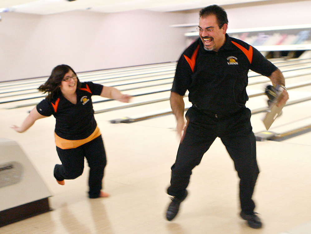 "Charlotte Johnson, 17, chases head coach Oscar Garnica around the bowling alley after a match at Spare Time Lanes in Kennewick after Garnica playfully knocked over her stuffed lion ""Lionel"" she got as a present."