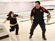 """Charlotte Johnson, 17, chases head coach Oscar Garnica around the bowling alley after a match at Spare Time Lanes in Kennewick after Garnica playfully knocked over her stuffed lion """"Lionel"""" she got as a present."""