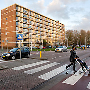 Nederland Rotterdam 19 december 2008 20081219 Foto: David Rozing ..Deelgemeente IJsselmonde, allochtone moeder steekt zebrapad over met kind in buggy.Mother and child crossing the street..Foto: David Rozing