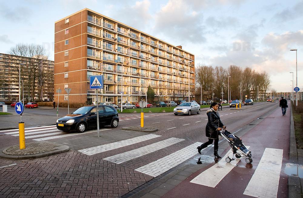 Nederland Rotterdam 19 december 2008 20081219 Foto: David Rozing ..Deelgemeente IJsselmonde, allochtone moeder steekt zebrapad over met kind in buggy.Mother and child crossing the street..Foto: David Rozing