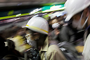People wait for buses home from Shibuya, some wearing helmets for safety, after a magnitude .9 earthquake hit the Tohoku region of north east Japan causing tremors in Tokyo that stopped the train and cellphone networks. Many people were stranded in the centre of Tokyo over night. Tokyo, Japan Friday March 11th 2011