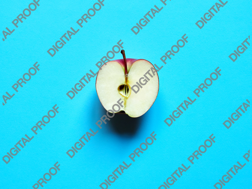 Apple fruit sliced by half isolated in studio over a light blue background