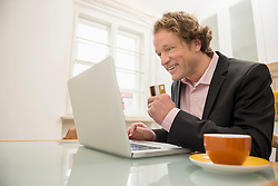 Man in suit with laptop and credit card